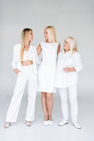 full length view of three generation blonde women looking at each other on grey