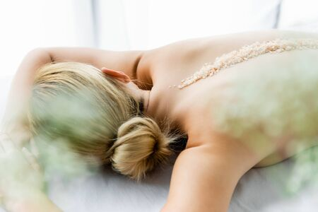 woman lying on massage mat with sea salt on back