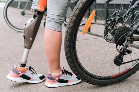 partial view of disabled sportswoman with bicycle on street Reklamní fotografie