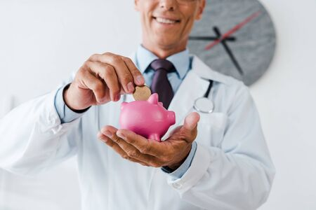 cropped view of happy doctor in white coat putting coin in piggy bank Banque d'images - 131826877