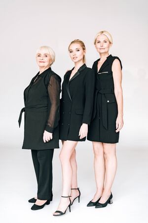 full length view of fashionable three-generation blonde women in total black outfits isolated on grey 스톡 콘텐츠