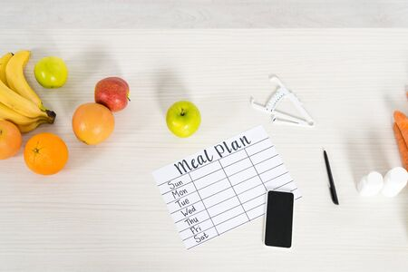 top view of meal plan, smartphone with blank screen, caliper, pills and fresh fruits on wooden surface Stockfoto