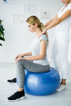 chiropractor touching shoulders of attractive patient on blue exercise ball
