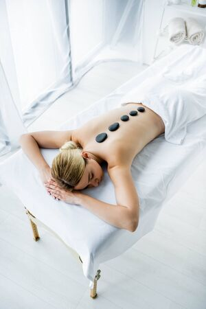 high angle view of attractive woman with hot stones on back lying on massage mat 版權商用圖片