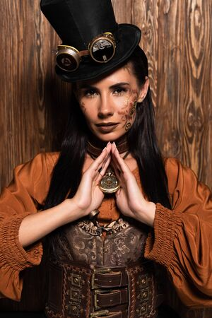 attractive woman with steampunk makeup touching medallion on wooden