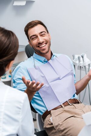 selective focus of cheerful patient gesturing and looking at dentist