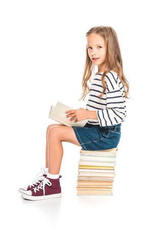 kid in denim skirt sitting on books and reading on white