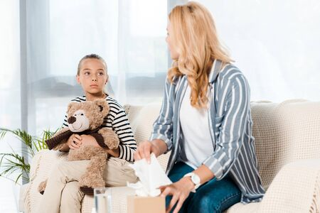 kid with teddy bear looking at sick mother taking tissue at home 写真素材