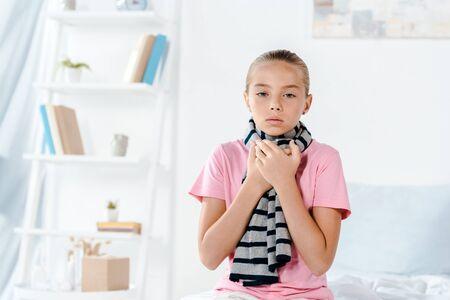 sad and sick kid having sore throat while looking at camera