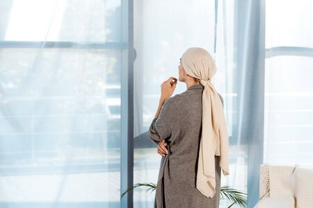 sick woman with head scarf standing in living room near windows