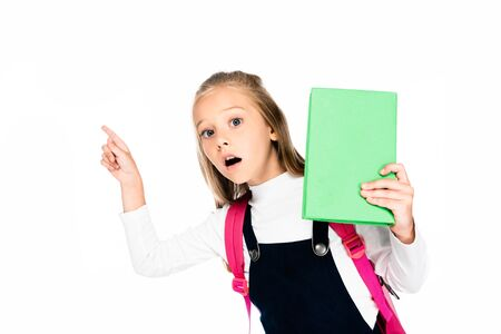 surprised shoolgirl pointing with finger while holding book and looking at camera isolated on white