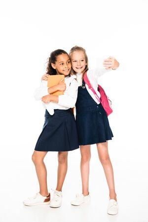 full length view of happy schoolgirl hugging african american friend and taking selfie on white background 写真素材 - 132010402