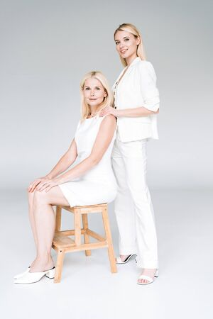 smiling blonde young daughter embracing mature mother in total white clothes on wooden chair on grey