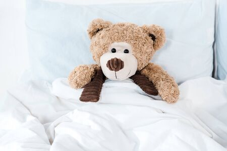soft toy in bed with white bedding and pillows