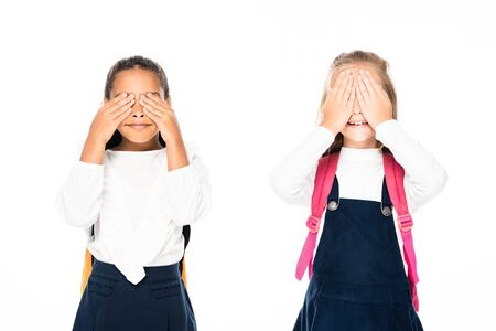 two multicultural schoolgirls covering faces with hands isolated on white 写真素材