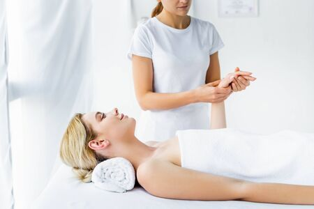 cropped view of masseur doing hand massage to attractive woman  Stok Fotoğraf