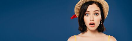 panoramic shot of shocked girl in straw hat isolated on blue Imagens