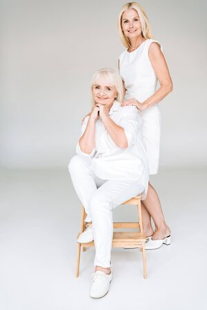 full length view of elegant blonde mature daughter and senior mother in total white outfits