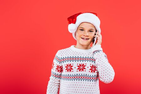 front view of smiling kid in santa hat talking on smartphone isolated on red