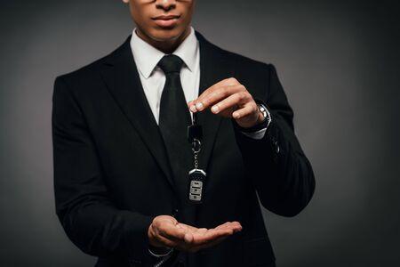 Teilansicht eines afroamerikanischen Geschäftsmannes, der Autoschlüssel auf dunklem Hintergrund zeigt