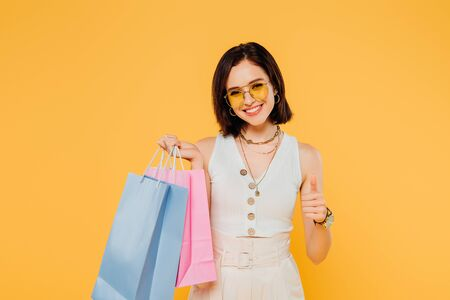 happy fashionable girl in sunglasses holding shopping bags and showing thumb up isolated on yellow