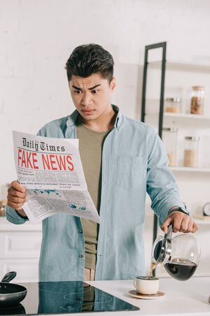 shocked asian man reading fake news newspaper while pouring coffee in cup Imagens