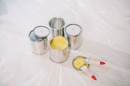 cans with paint and yellow paintbrushes on white floor covered with cellophane