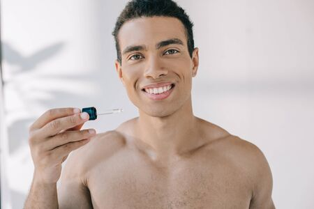 handsome mixed race man holding pipette with serum, smiling and looking at camera
