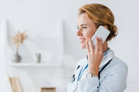 happy doctor smiling while talking on smartphone in clinic