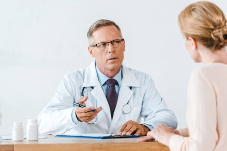 selective focus of doctor in white coat looking at woman and gesturing while sitting near table