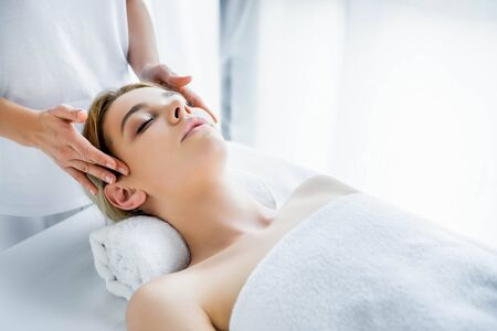 cropped view of masseur doing face massage to attractive woman