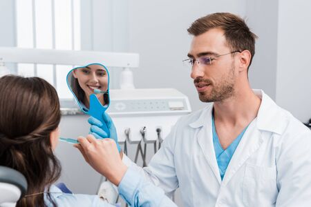 selective focus of girl brushing teeth and looking at mirror near handsome dentist