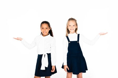 two cute multicultural schoolgirls pointing with hands while smiling at camera isolated on white