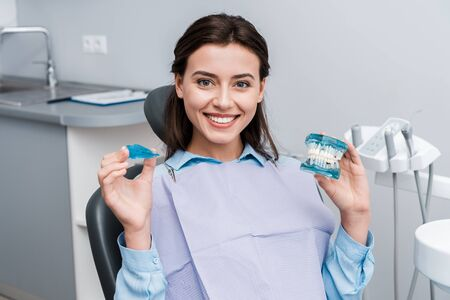 cheerful young woman holding teeth model and retainer in hands