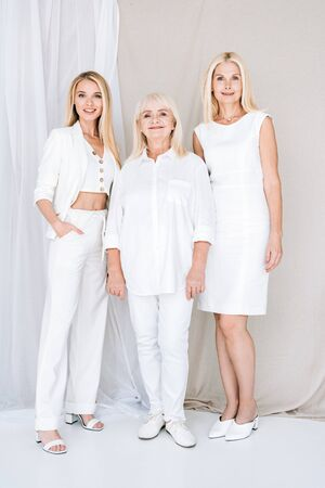 full length view of three generation blonde women in total white outfits