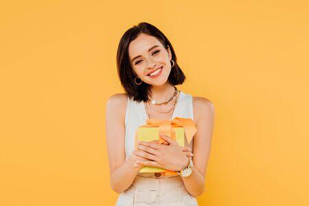 glückliches lächelndes Mädchen, das Geschenkbox lokalisiert auf Gelb hält
