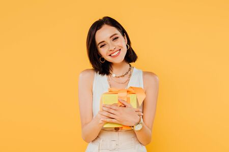 happy smiling girl holding gift box isolated on yellow Archivio Fotografico