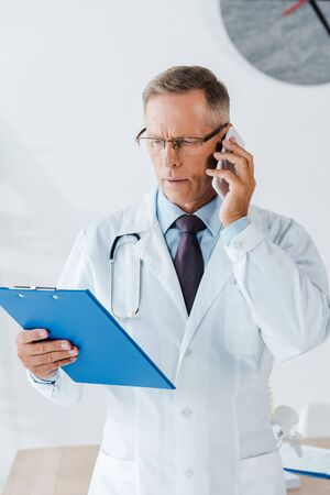 serious doctor in glasses looking at clipboard and talking on smartphone 写真素材