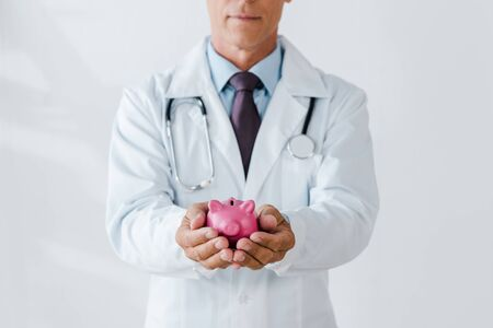 cropped view of doctor holding pink piggy bank in hands on white