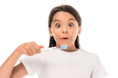 surprised kid looking at camera and holding toothbrush isolated on white Imagens