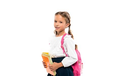 cheerful child holding books and standing with backpack isolated on white