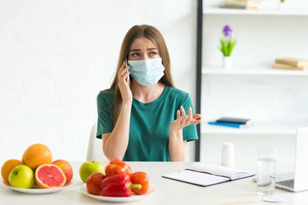 girl in medical mask talking on smartphone at table with fruits, vegetables and pills at home Archivio Fotografico