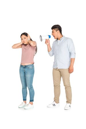 irritated asian woman yelling at girlfriend into megaphone on white background Stok Fotoğraf