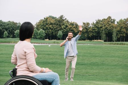 happy man talking on smartphone and waving hand to disabled girlfriend Banco de Imagens