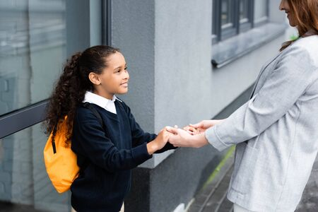 cropped view of woman holding hands of happy, adopted african american daughter going to school