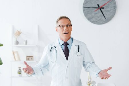 surprised doctor in white coat and glasses gesturing in clinic