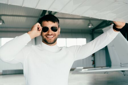 front view of smiling bearded man in sunglasses standing near plane Banco de Imagens