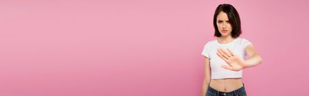 panoramic shot of beautiful serious girl showing stop gesture isolated on pink