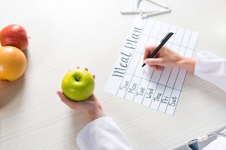 cropped view of dietitian holding apple and writing in meal plan at workplace
