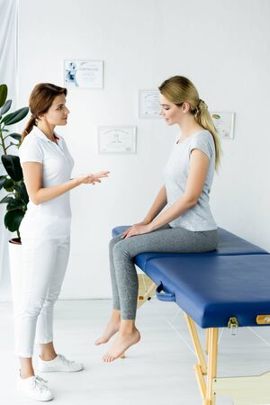 chiropractor talking with attractive patient in t-shirt in clinic